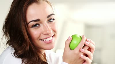 stock-footage-joyful-young-woman-eating-green-apple-is-healthy